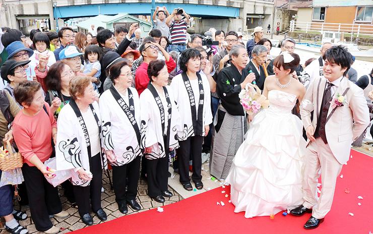 新湊めでた保存会のメンバーら住民に祝福される(右から)米田哲也さんと下村かおりさん