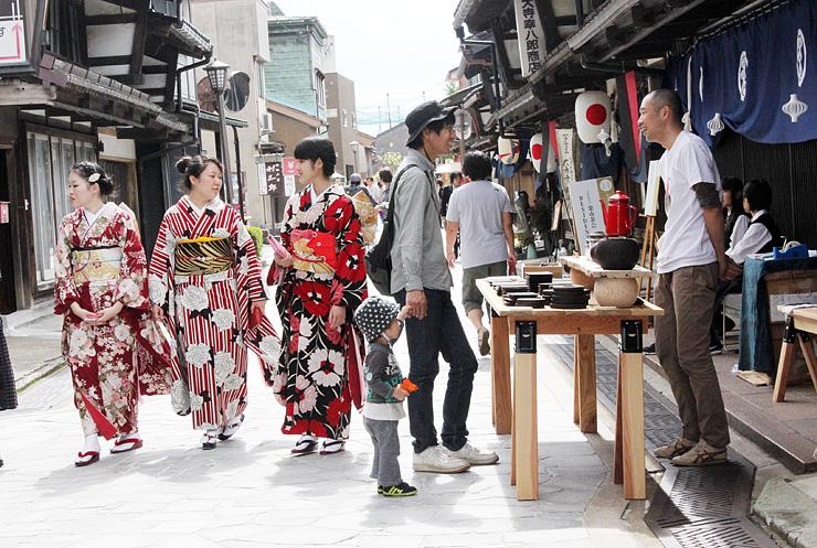 さまざまな工芸品が展示販売され、着物姿の女性や親子連れらが行き交う石畳通り=高岡市金屋町