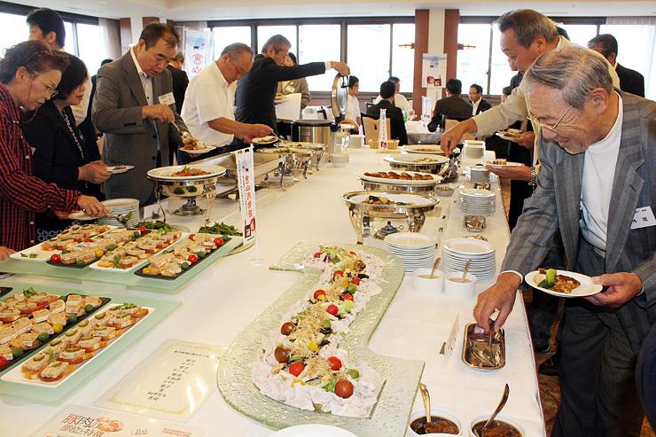 県産豚肉を使った料理を楽しむ参加者=県民会館
