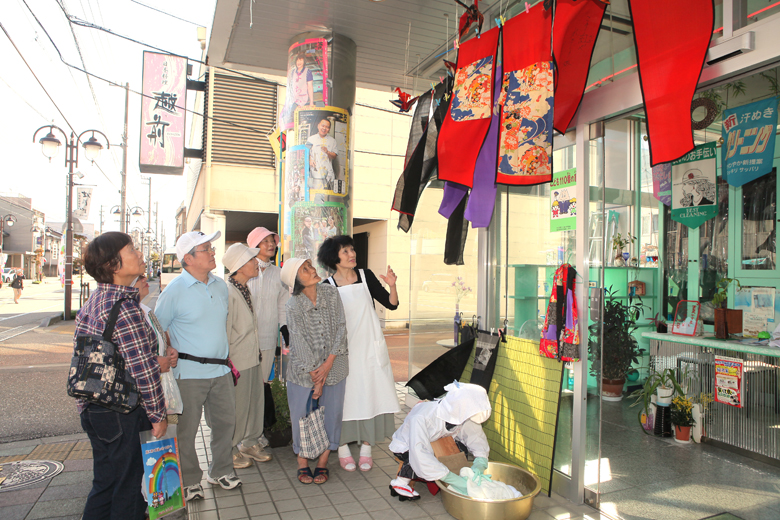 のれん(右上)や洗濯姿の女性の人形(中央下)を並べた店=小矢部市中央町