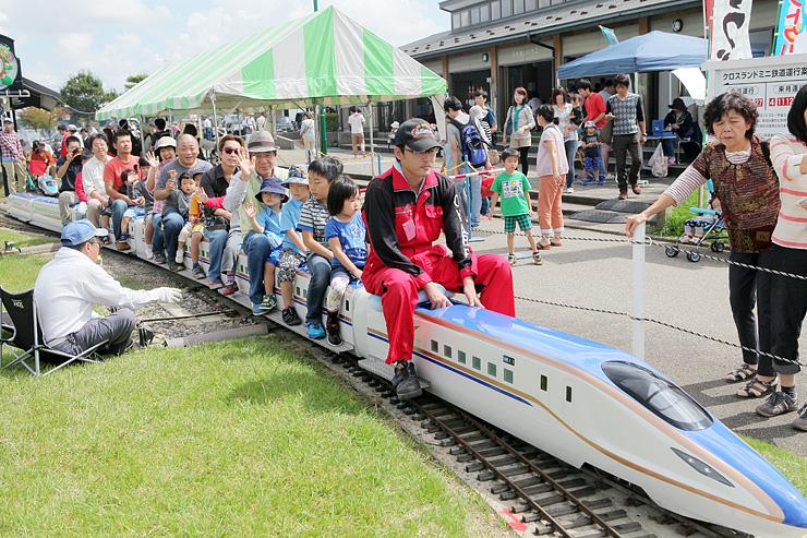 北陸新幹線のミニ鉄道に乗車する親子ら=クロスランドおやべ
