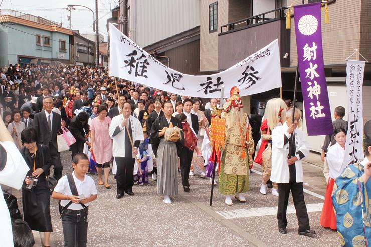 「稚児社参」で射水神社までの道を練り歩く2000人以上の参加者=高岡市大手町