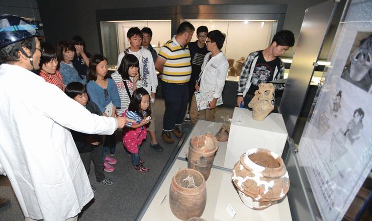 クイズの答えを探しながら、土器などの展示物を見る参加者たち=21日、茅野市尖石縄文考古館