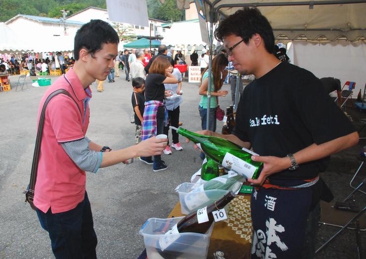 オリジナルちょこに試飲用の日本酒を注いでもらう参加者(左)