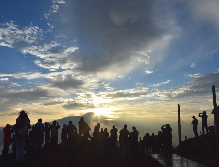 蓼科山から昇る日の出を眺める観光客ら=21日午前5時55分、茅野・諏訪市境の車山山頂