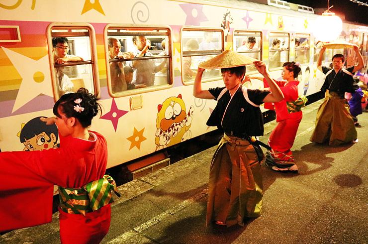 ホームで踊りを披露し、列車利用の観光客を見送る栄町の踊り手=JR城端駅