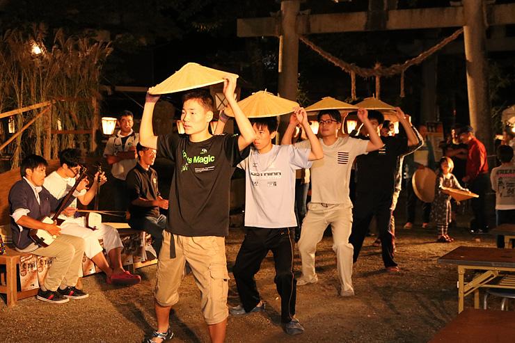 前夜祭で麦屋節の笠踊りを楽しむ地元の若者ら=地主神社