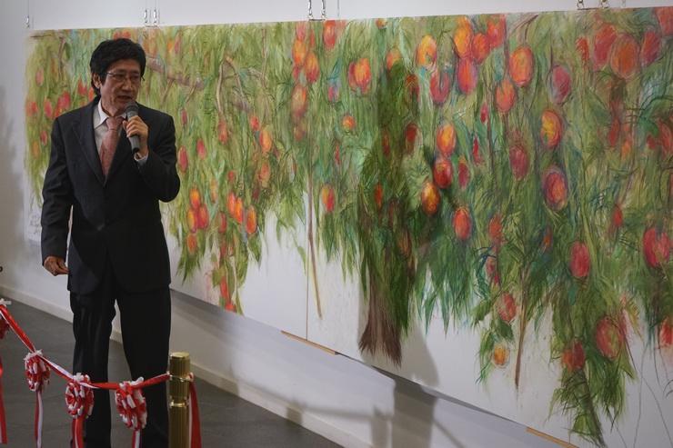 リンゴ畑を題材にした壁画の完成披露会であいさつする田窪さん=22日、飯綱町