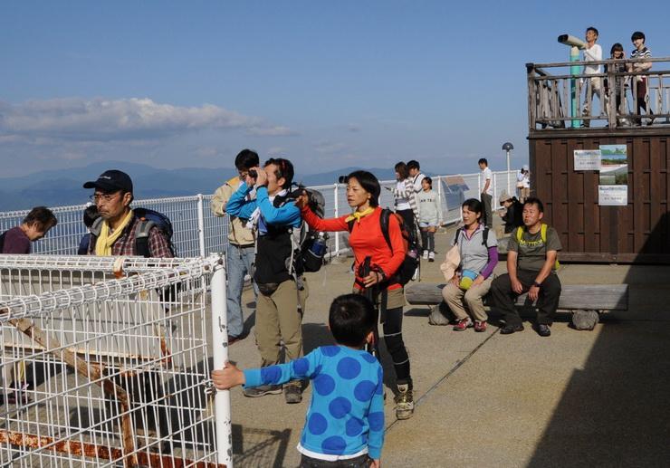 御岳ロープウェイの山頂側の駅から御嶽山の方向を見つめる人たち=22日午後3時1分、木曽町