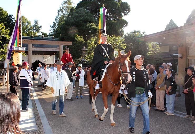60年ぶりの騎馬が加わっての「神輿渡御」で、二上射水神社へ向け出発する松本宮司(手前)、穴田会長(奧)ら=射水神社