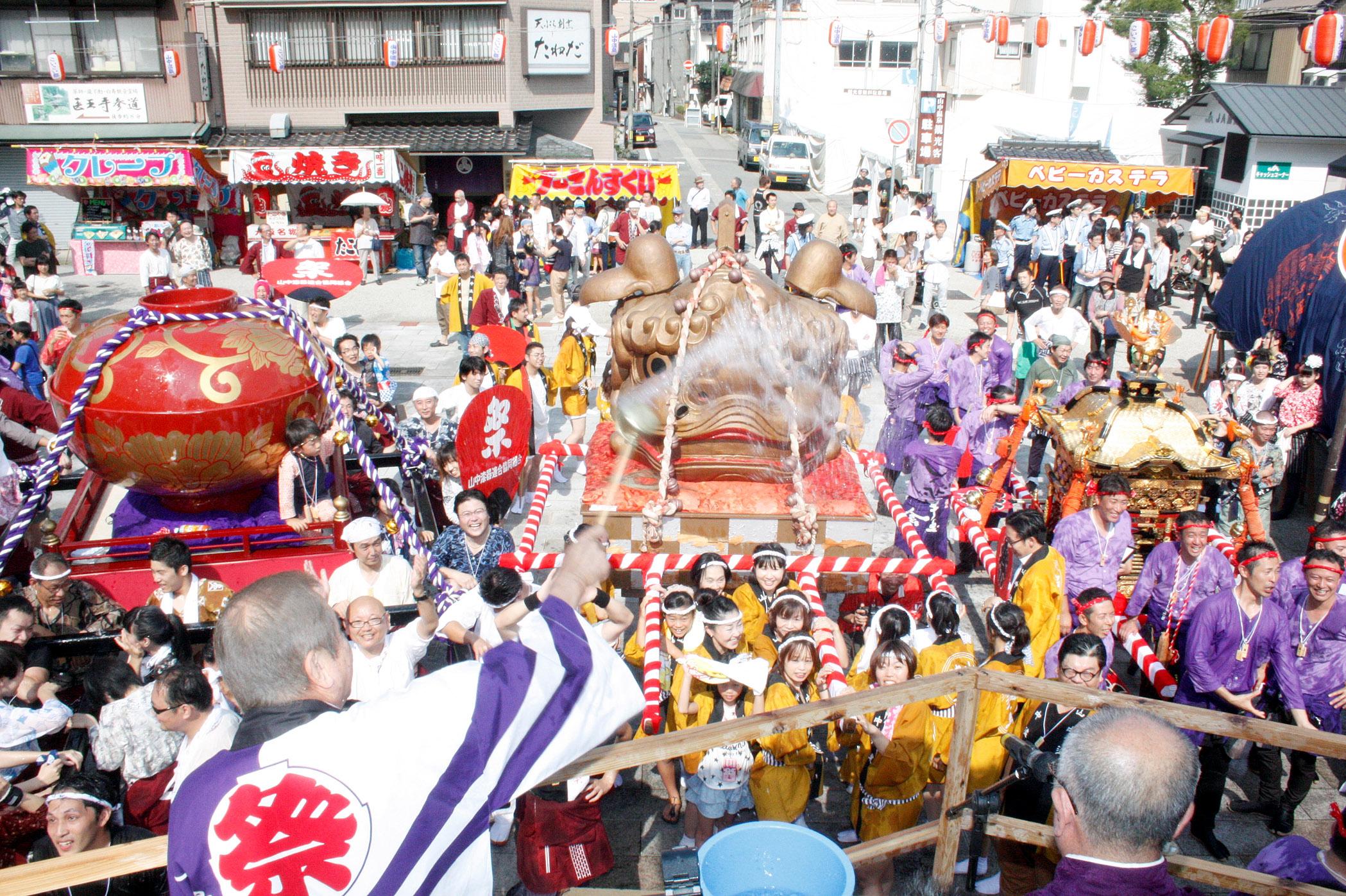 入湯の儀で源泉を浴びるみこし=加賀市山中温泉
