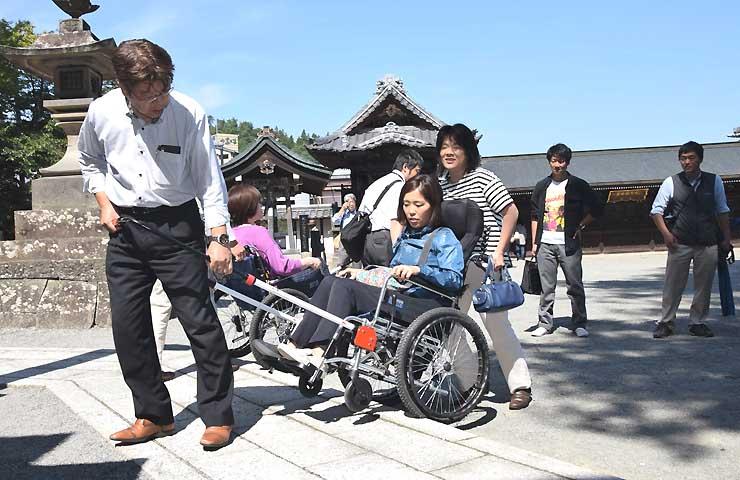 通路に一部段差のある北向観音の境内で、車いすに試乗する参加者ら