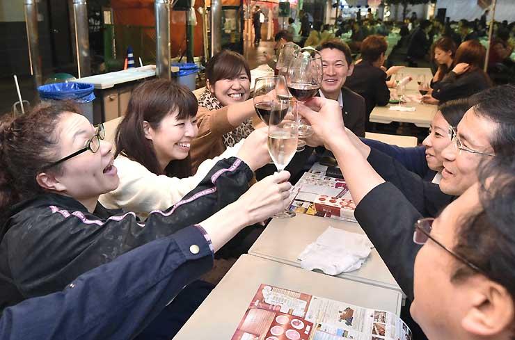 ワインサミットの会場で、好みのワインで乾杯する来場者たち=25日夜