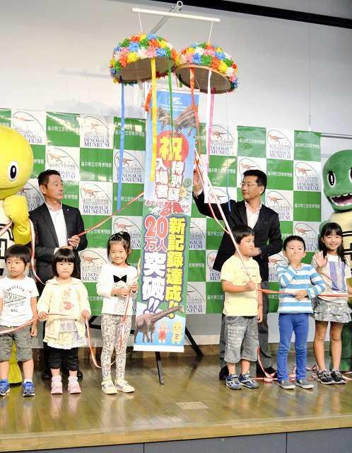 くす玉を割って入場20万人突破を祝ったセレモニー=26日、福井県勝山市の県立恐竜博物館