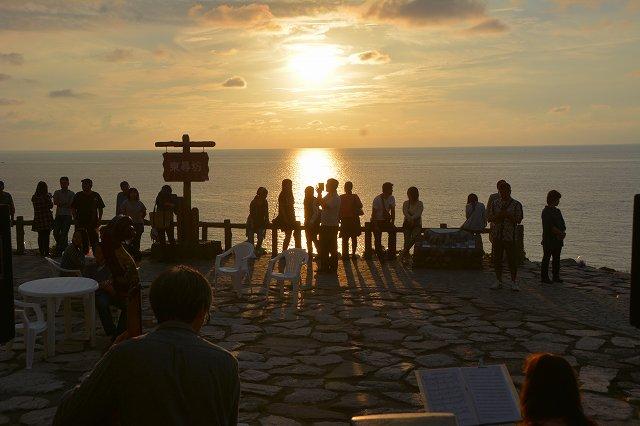 ジャズの演奏に耳を傾けながら水平線に沈む夕日を眺める観光客ら=26日、福井県坂井市三国町の東尋坊
