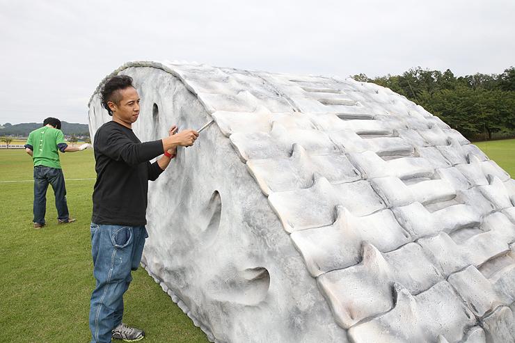 立体作品の設置作業を進める清河さん=富山市猿倉山森林公園芝生広場