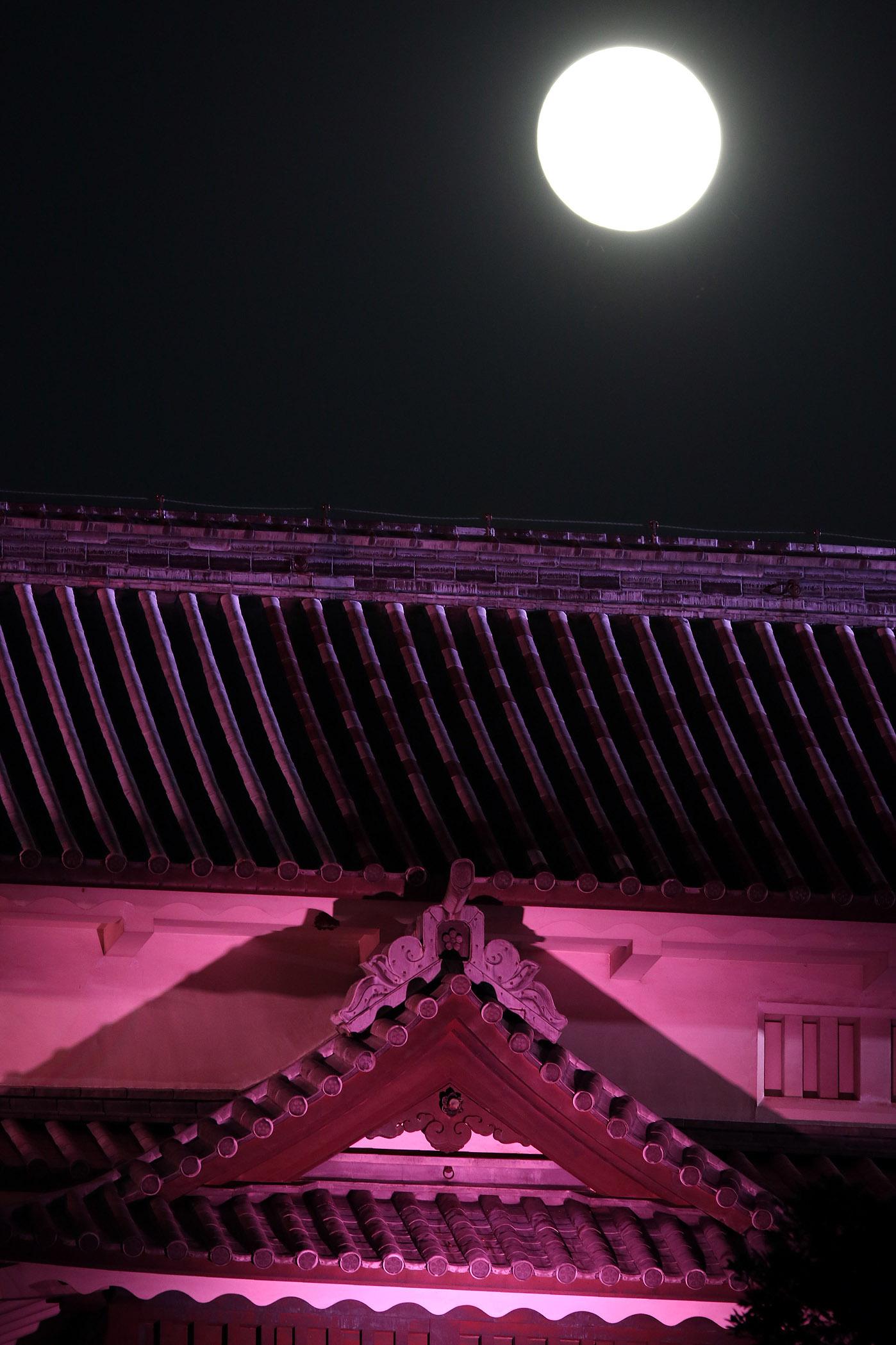 ライトアップされた三十間長屋の上空に浮かぶ中秋の名月=27日午後6時半、金沢城公園玉泉院丸庭園から撮影