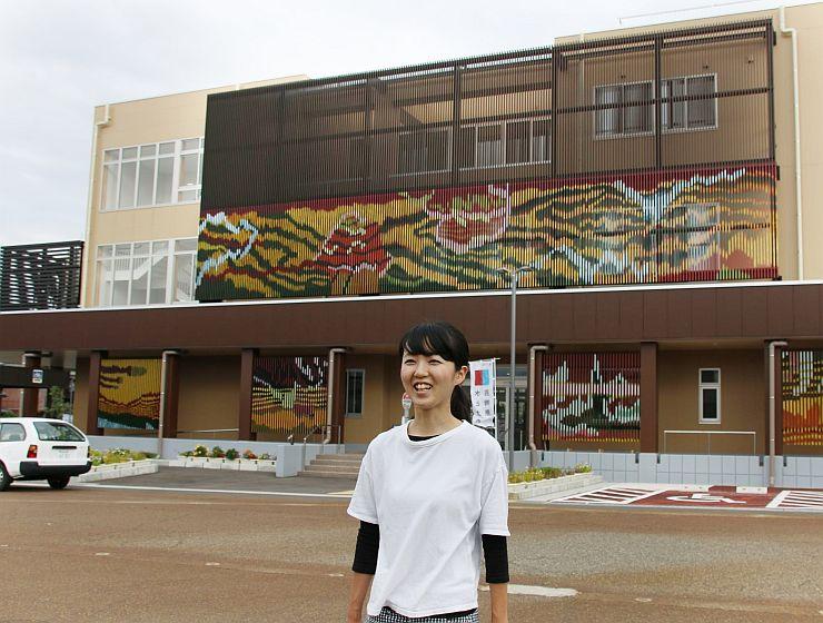 小須戸まちづくりセンターに描かれた壁画と作者の野原万里絵さん=新潟市秋葉区