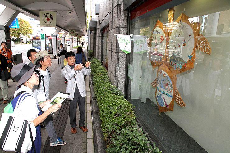 オフィスのウインドーに展示された作品を日比野克彦さんらが見て回った公開審査=26日、新潟市中央区