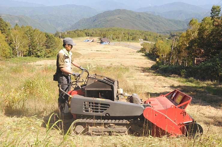 スキー場「おんたけ2240」の営業開始に向けて行われているゲレンデの草刈り作業=29日、王滝村