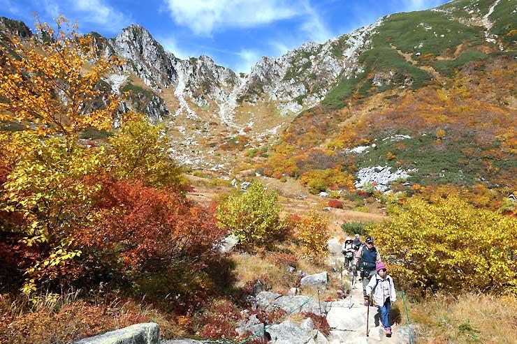 青空の下、山々に囲まれて紅葉が広がる千畳敷
