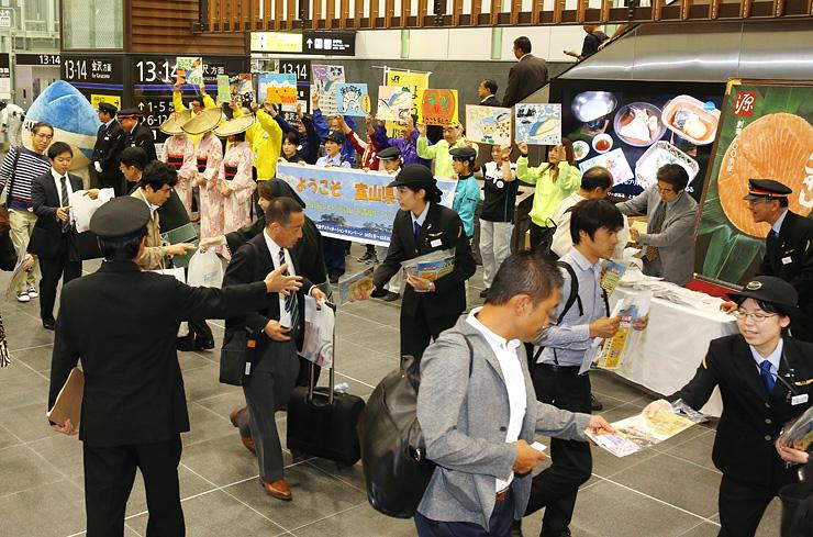 観光パンフレットなどを配布し観光客を出迎えるJR西日本の社員ら=JR富山駅