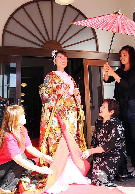 打ち掛けの着付けリハーサルをするモデルの仁保さんと花庵のメンバー
