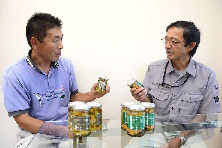 完成した瓶詰めを手に話す小池代表(左)と佐々木社長