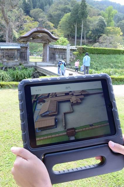 唐門上空から見た建物群の再現画像が流れるタブレット端末=3日、福井市の一乗谷朝倉氏遺跡