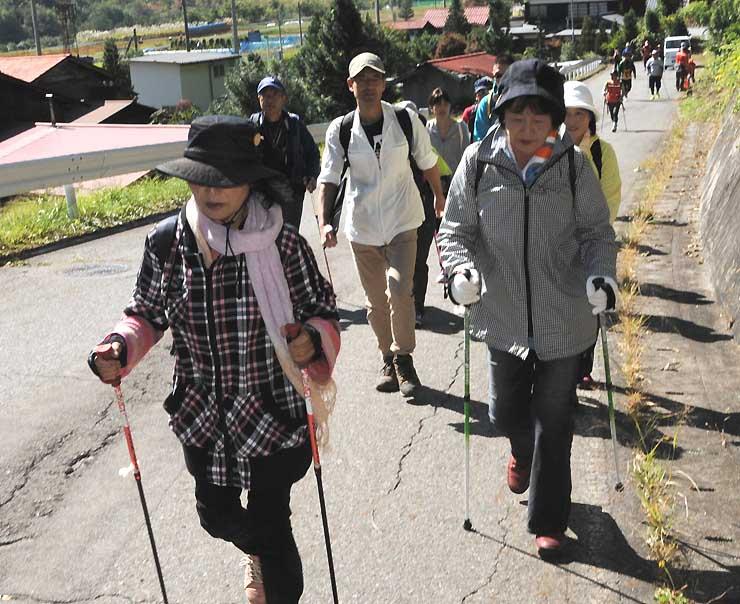 王滝村内をポールなどを持って歩く「王滝村おんたけ復興ウオーク」の参加者たち