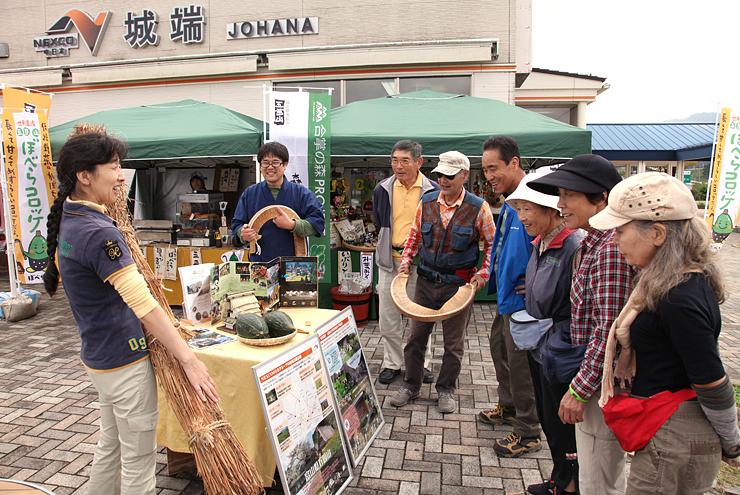 茅を手に観光客へ五箇山の魅力を語る中日本高速道路の小田切さん(左)