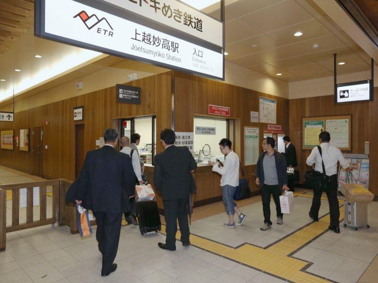 北陸新幹線下り最終便を降り、トキめき鉄道の改札へ向かう乗り換え客=1日午後10時すぎ、上越市の上越妙高駅