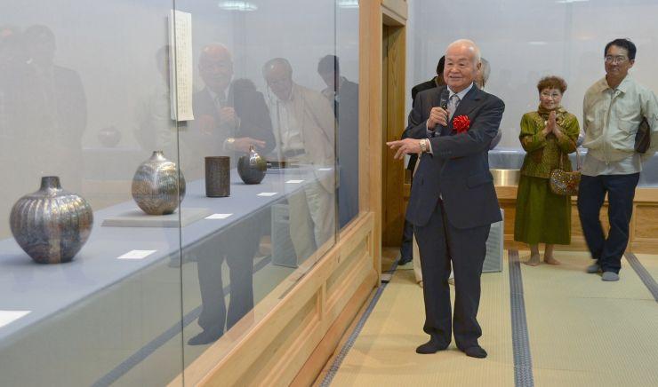 展示されている作品について解説する玉川宣夫さん=3日、新潟市西区