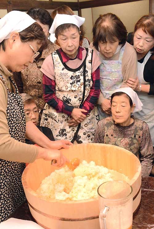 杏おこわの料理講習会で、内山さん(左)から作り方を聞く参加者たち