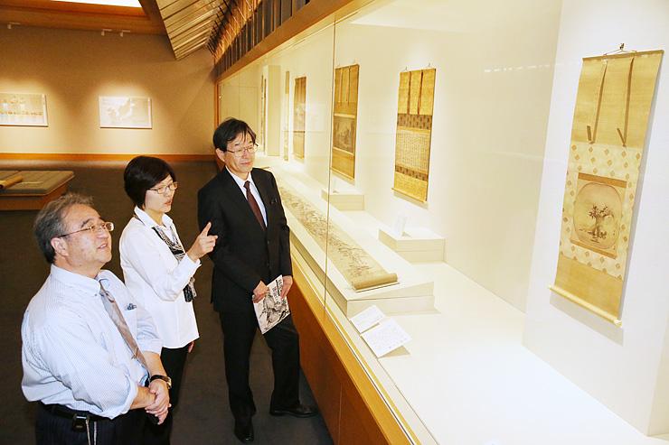 重要文化財の「倣玉澗山水図」など、作品の展示状況を確認する守安館長(右)=県水墨美術館