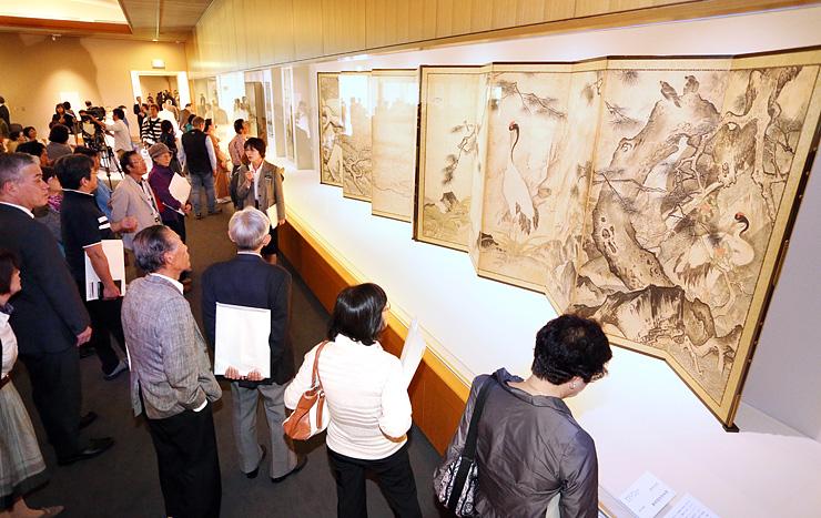 重要文化財「四季花鳥図屏風」など、水墨画を日本独自の表現に発展させた雪舟の名作に見入る来場者=県水墨美術館