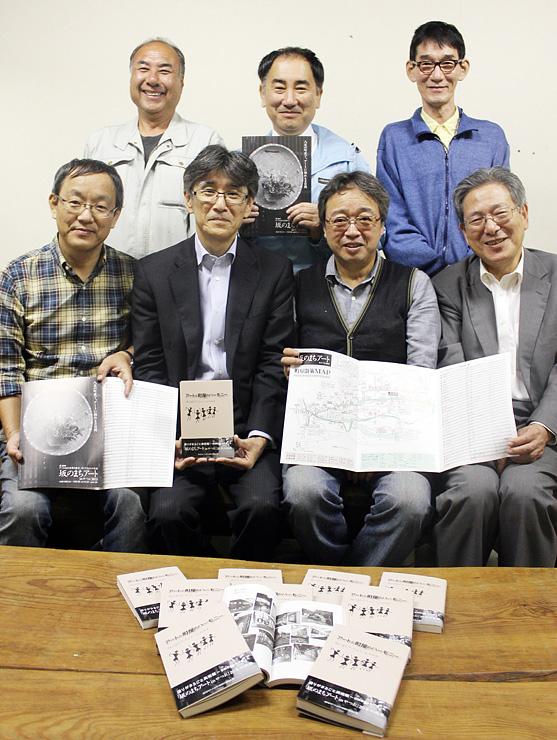 記念誌やパンフレットを手に笑顔を見せる実行委員会メンバー