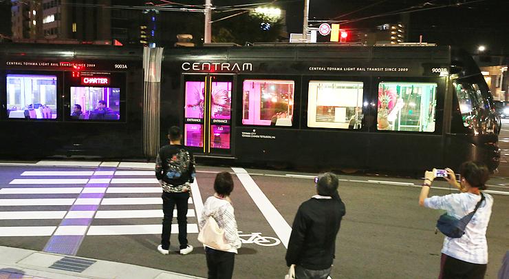 カラフルな光を発しながら走る「ライトラム」=JR富山駅前