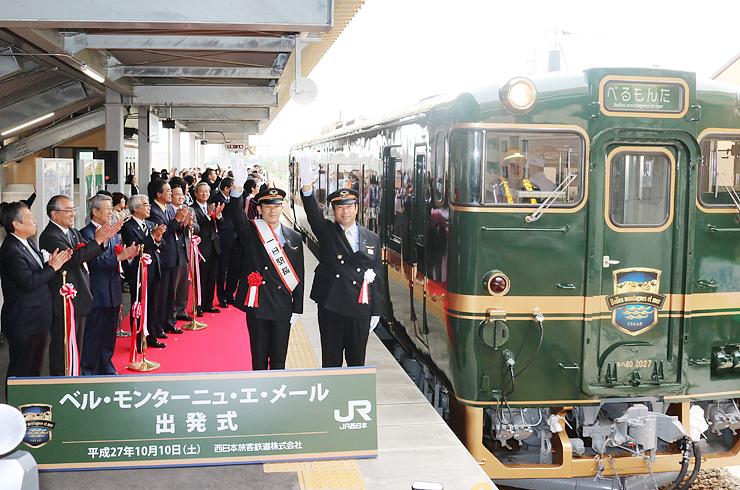 大勢の人に見守られ、西村さん(中央左)らの合図で出発する観光列車「べるもんた」=城端線新高岡駅