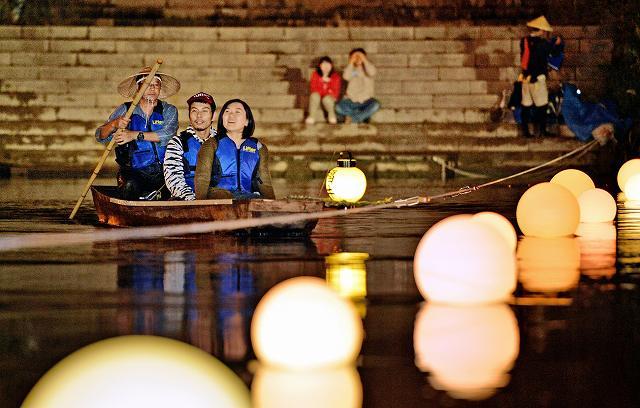 「毛矢の繰舟」の夜間航行を楽しむ人たち=11日、福井市の九十九橋上流