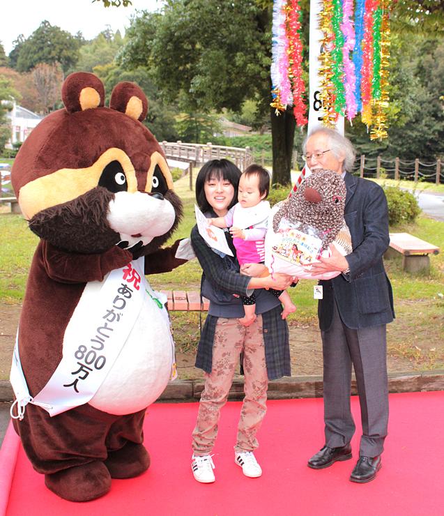 800万人目の入園者となり山本園長(右)から記念品を贈られる本田さん親子=ファミリーパーク