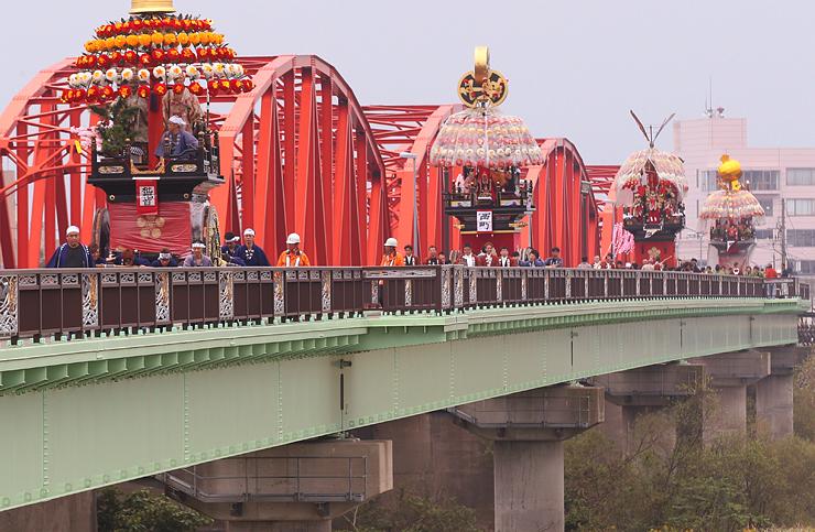 大門大橋を4基が連なって渡る曳山=射水市枇杷首から