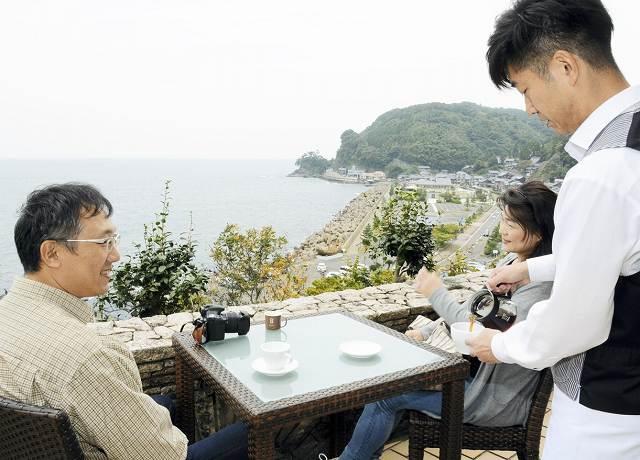 海の見えるテラス席でコーヒーを待つ来場者=11日、福井県南越前町河野の北前船主の館・右近家「西洋館」