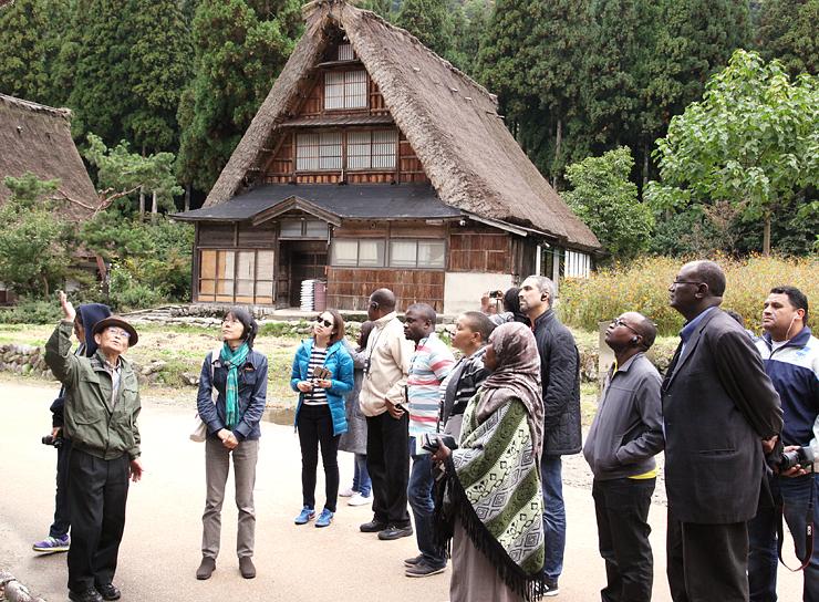 北さん(左)の案内で菅沼集落を視察する研修参加者