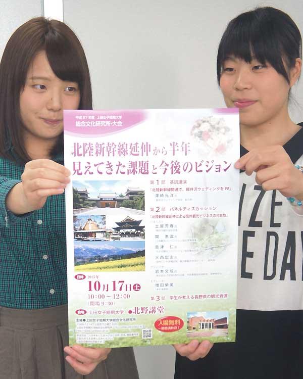 シンポジウムのポスターを持つ上田女子短大の学生