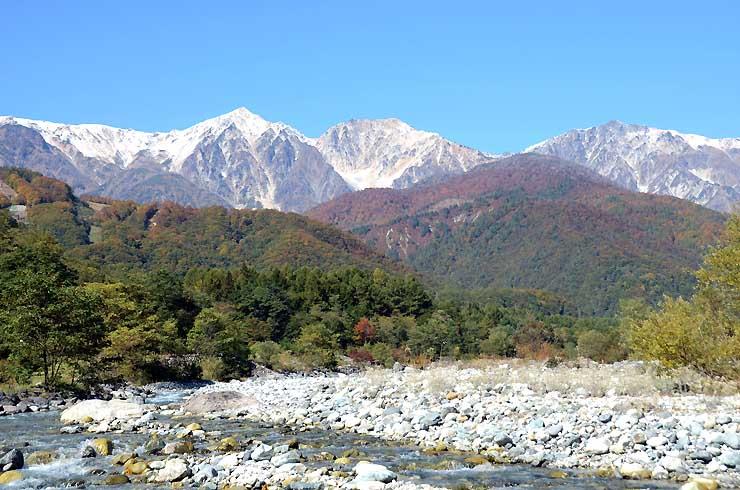 雪の白、紅葉の赤、里の緑が織りなす「三段紅葉」=15日、白馬村北城の白馬大橋近く