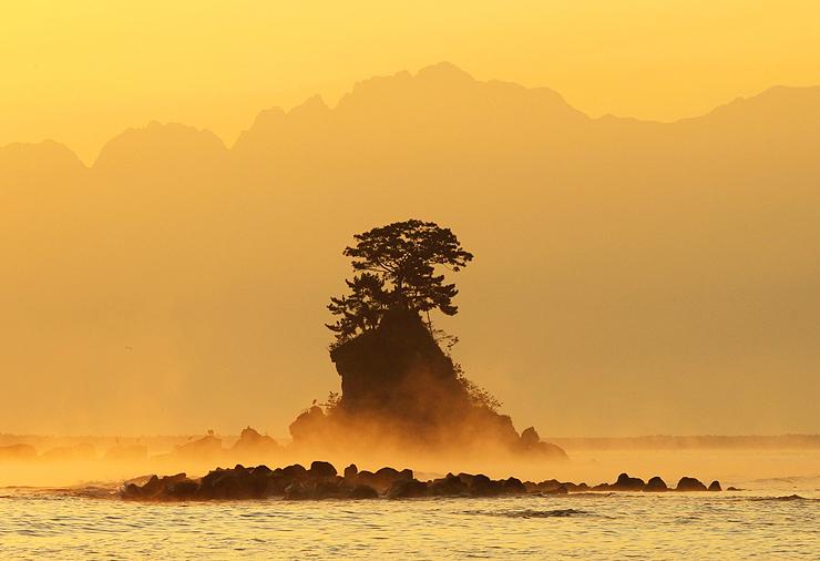 海上に立ち上る気嵐。剱岳の稜線を背景に女岩(中央)周辺が金色に染まった=15日午前6時13分、雨晴海岸