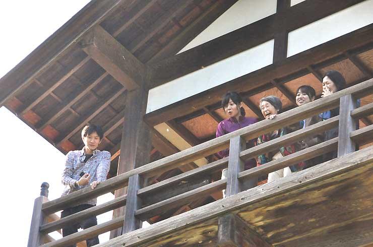 滝見台で暮白の滝を目がけて皿を投げる参加者たち