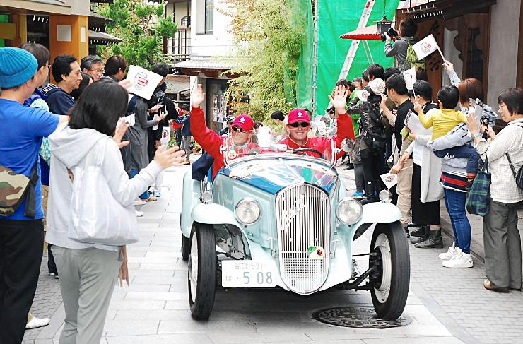 沿道の観衆の声援に応えながら渋温泉の石畳の道を走るクラシックカーの運転手ら