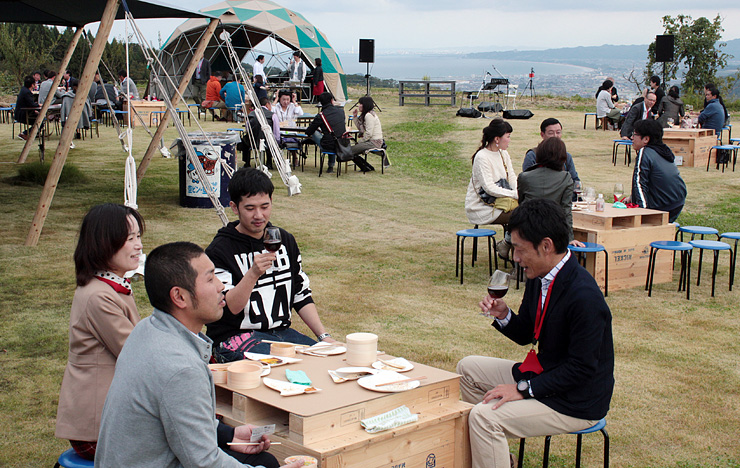 眺めの良い芝生広場でワインと料理を楽しむ来場者